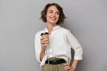 Wall Mural - Photo of positive woman 20s smiling and holding takeaway coffee, isolated over gray background