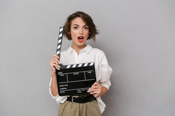 Wall Mural - Photo of gorgeous woman 20s smiling and holding black clapperboard, isolated over gray background