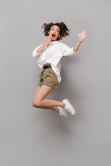 Wall Mural - Full length image of young girl 20s smiling and jumping, isolated over gray background