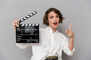 Wall Mural - Photo of young woman 20s smiling and holding black clapperboard, isolated over gray background