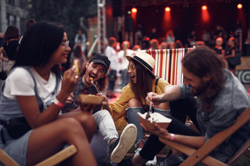 Portrait of cheerful hipster girl in hat feeding boyfriend with fork while sitting on folding chair. Blurred bearded man and girl in glasses eating and smiling
