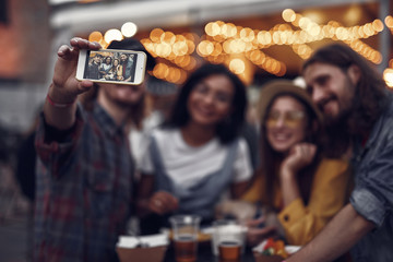 Hipster friends taking photo with smartphone while standing at the table in outdoor cafe. Focus on phone display with picture