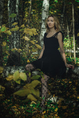 A young kind witch in a black dress with a black mask in a mystical forest in various poses. Art processing