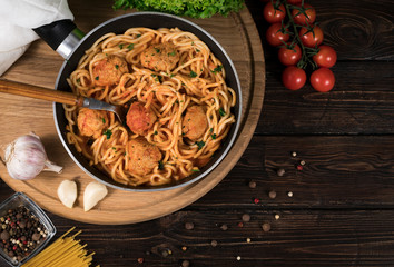 spaghetti and tomatoes on wooden background