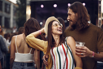 Waist up portrait of beautiful couple enjoying company of each other at concert. Girl in hat looking at bearded man with beer while he hugging her from behind