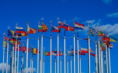 Flags of European countries on flagpoles against the blue sky.