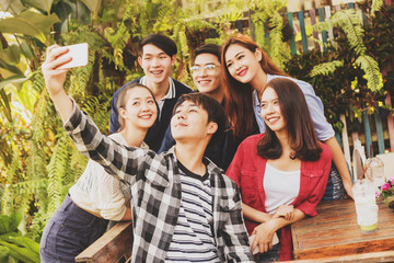 Group of six teenagers taking selfie with fun together in afternoon