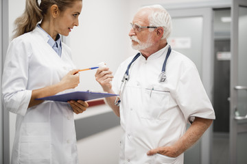 Waist up portrait of medical workers discussing treatment for patient. Young lady in white lab coat holding clipboard and looking at old therapist with stethoscope