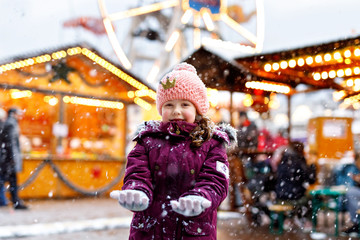 Little cute kid girl having fun on traditional Christmas market during strong snowfall. Happy child enjoying traditional family market in Germany