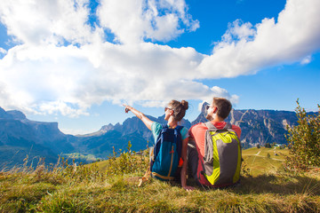 Hikers with backpacks sitting on top of a hill and enjoying mountains view. Dolomiti, Alta Badia