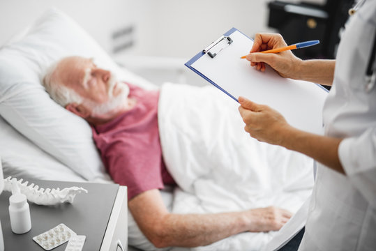 Female therapist filling up medical form while standing near nightstand with medications in hospital room. Old man sleeping on blurred background