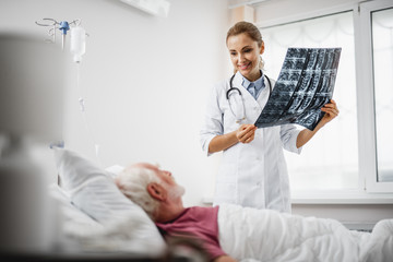Good news. Portrait of beautiful young lady in white lab coat sharing radiography results with old man. Gentleman lying in hospital bed