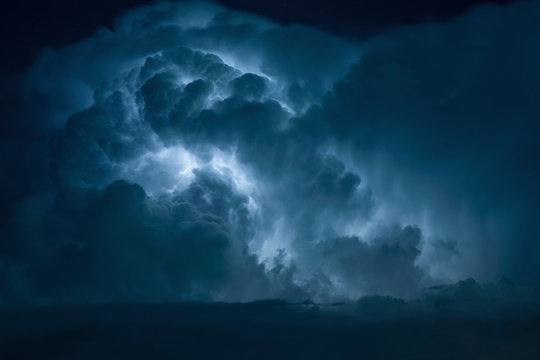 Blue Lightning strike surrounded by storm clouds.