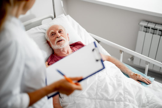 Thank you for your concern. Top view portrait of old man resting in hospital room and chatting with female therapist. Focus on bearded gentleman