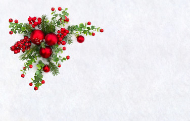 Christmas decoration. Twigs christmas tree, christmas red balls and red berries on snow with space for text. Top view, flat lay