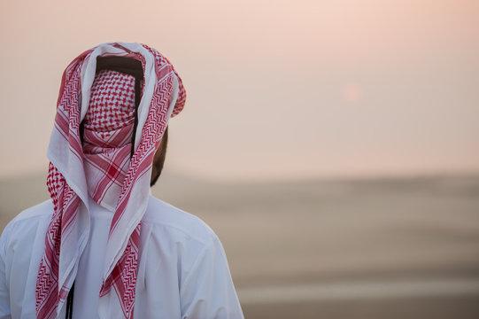 Arab man in the desert is meeting sunrise