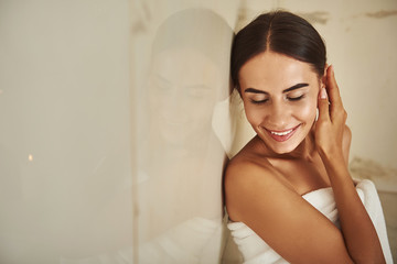Beautiful dark haired young woman covered in white towel and smiling while touching her ear in hammam