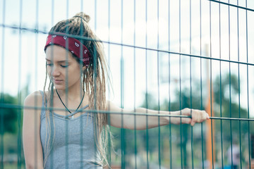 Calm lady thoughtfully looking down and touching the chain link fence