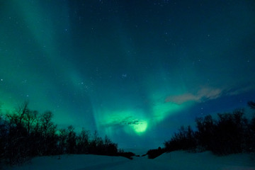 Colorful northern lights glowing over the beautiful snowy wilderness in Finland.