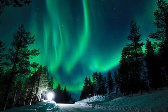 Bright lamp shining on the empty snowy road just as the northern lights appear.