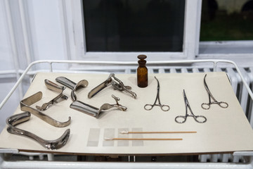 Old gynecology and obstetrics tools, instruments and devices on display in a historic hospital, including various speculums, Axis, scissors and forceps