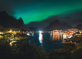 Northern lights Aurora Boreals over illuminated fishing village of reine lofoten islands.