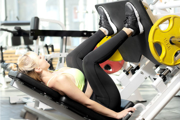 Young woman  trains her legs on a sports simulator in the gym.Girl exercing her legs at a health club
