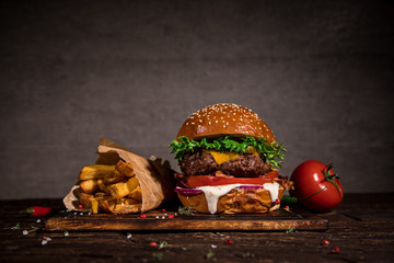 Tasty burger with french fries on wooden table.