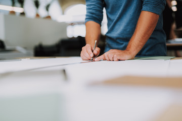 Close up of a male designer being involved in making a drawing while standing near table