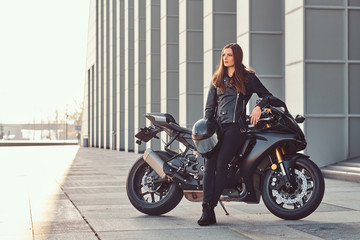 A beautiful biker girl leaning on her superbike outside a building on a sunny day. Wall mural