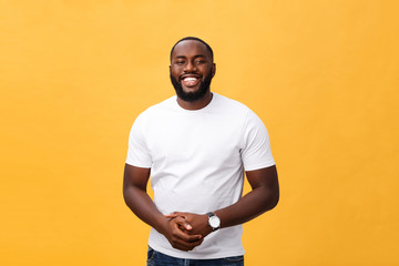 Portrait of delighted African American male with positive smile, white perfect teeth, looks happily at camera, being successful enterpreneur, wears white t shirt.