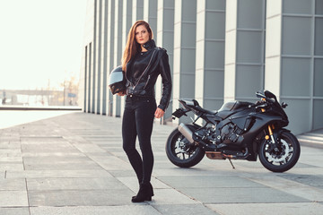 A beautiful biker girl holding helmet next superbike outside a building.