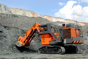 An orange power-shovel works in a career
