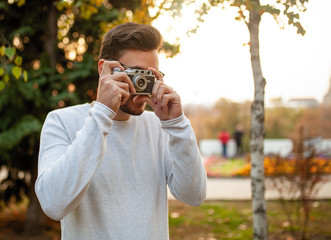 Young handsome hipster guy walks in a beautiful autumn park on the background of yellow leaves in warm sunny weather and takes pictures on a pig film camera. Autumn leisure time. Creative youth