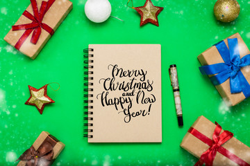 Notebook with with text Merry Christmas and Happy New Year and Christmas-tree decorations, toys and gift boxes on green background. Flat lay, top view