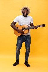 Full-length photo of excited artistic man playing his guitar in casual suite. Isolated on yellow background.