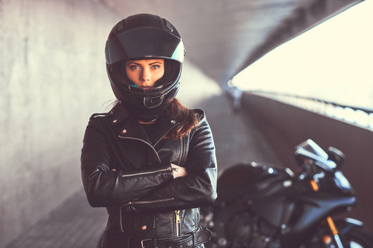 Close-up portrait of a biker girl with her arms crossed next to her superbike inside the bridge.