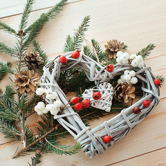 Christmas heart wreath with winter berries and branches of a Christmas tree on a wooden background
