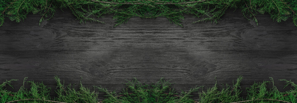 Christmas card. Black wood background with fir branches up and down, top view. Xmas rectangle congratulation.