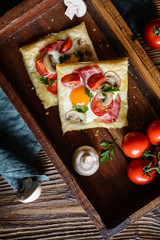 Puff pastry pies with egg, bacon, mushrooms and tomato