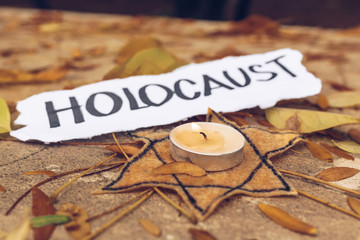 Inscription Holocaust. Star of David and candle on autumn leaves