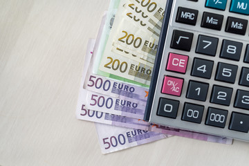 Euro banknotes with calculator on wooden desk