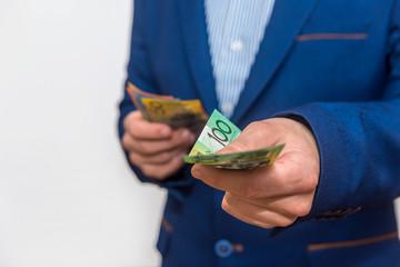 Male hands offering australian dollar banknotes, macro