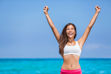 Happy fitness success woman winner. Asian girl cheering arms up of joy on summer beach.
