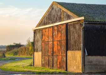 Barn on farmland with metal red and rusty doors.