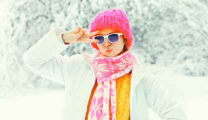 Fashion cool girl in colorful knitted hat, scarf having fun on snowy background