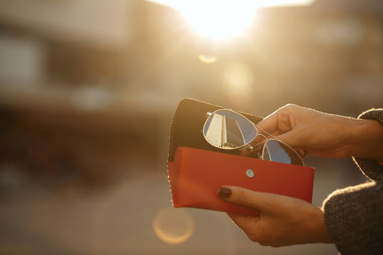 Closeup shot of female hand opening red glasses case at the background of sun. Empty space
