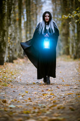 Photo of witch woman with burning blue lantern in hands