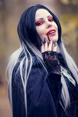 Portrait of vampire girl with stream of blood at mouth with red eyes