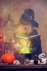 Photo of witch with pumpkin and book of spells at table with pot of steam